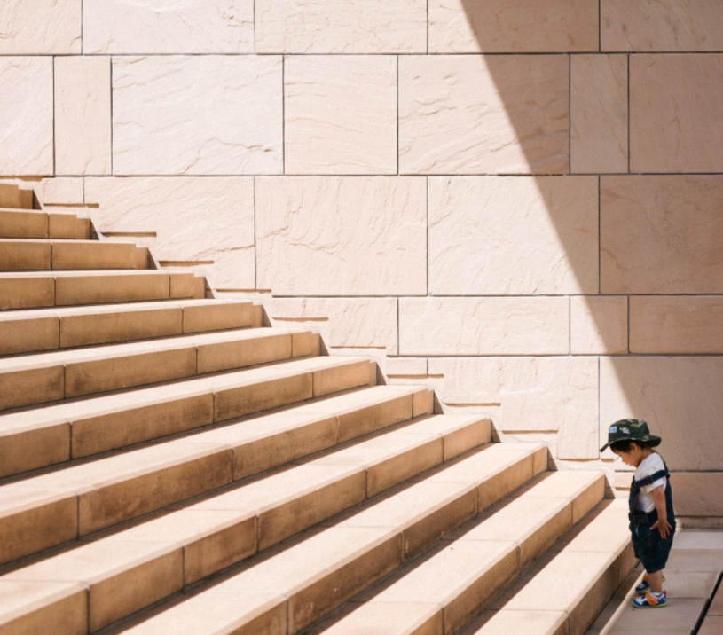 Image of a small boy at the bottom of some high steps