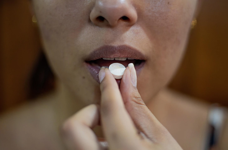 Photo of a woman taking a white pill